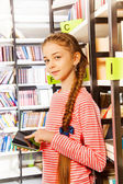 Girl holds tablet  in library — Stock Photo