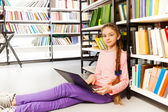 Girl with laptop in library — Stock Photo