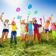 Jumping kids with flying balloons in summer — Stock Photo #48544925