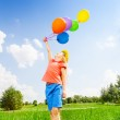 Girl with colorful balloons wears flower circlet — Stock Photo #48545107