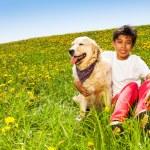 Smiling boy hugs cute dog sitting on green grass — Stock Photo #48545145
