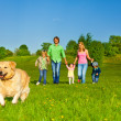 Family walks with running dog in park — Stock Photo #48545221
