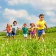 Running kids in green field during summer — Stock Photo #48545491