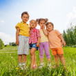 Four kids standing close to each other in meadow — Stock Photo