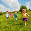 Running children in green field during summer — Stock Photo