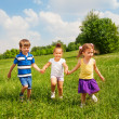 Three happy children holding hands and playing — Stock Photo