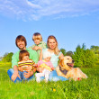 Family sitting on green grass with dog — Stock Photo #48546253