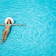 Girl with hat swimming in crystal-clear pool — Stock Photo #48546363
