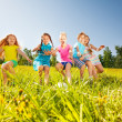 Happy children playing football in yellow meadow — Stock Photo #48546375