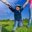 Happy kid holding parents hands in park — Stock Photo #48546499