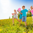 Excited children with balloons run in green field — Stock Photo #48546547