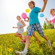 Happy children with balloons run in green field — Stock Photo #48546561