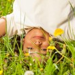 Cute curly boy stands upside down in field — Stock Photo