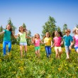 Playful children run, hold hands in green field — Stock Photo #48546653