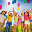 Kids stand in half round with arms up to balloons — Stock Photo #48546705