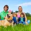 Happy family sitting on green grass with dog — Stock Photo #48546825