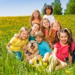 Cheerful kids with dog sitting on the grass — Stockfoto