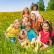 Cheerful kids with dog sitting on the grass — ストック写真