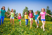 Happy children run and hold hands in green field — Stock Photo