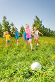Happy children playing football in green field — Stock Photo