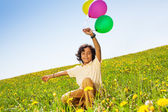 Positive boy with flying balloons in summer — Stock Photo