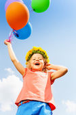 Positive girl with balloons wears flower circlet — Stockfoto