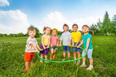 Six funny children holding one hoop together — Stockfoto