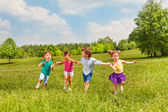 Four kids holding hands and standing together — Stockfoto