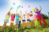 Children standing with arms up to flying balloons — Stockfoto