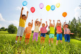 Happy kids with balloons and arms up in the sky — Stockfoto