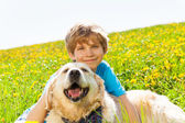 Smiling boy and funny dog sitting on grass — Foto Stock
