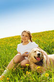 Smiling girl and funny dog sitting on grass — Foto Stock