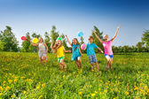 Happy five children with balloons run in field — Stock Photo