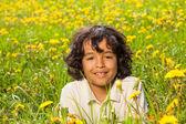 Cute curly boy in dandelions field — Stock Photo