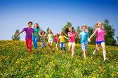 Running happy kids holding hands in green field — Stockfoto