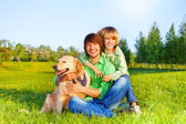 Smiling father, kid  and dog sit in park on grass — Stock Photo