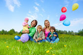 Smiling family sitting on grass with balloons — Stock Photo