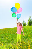 Happy girl with flying balloons stands on grass — Stockfoto