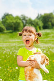 Excited small girl with open mouth hugging rabbit — Stock Photo