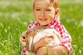 Cute girl cuddling rabbit in green field — Stock Photo