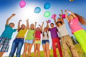 Children stand in semi-circle with balloons up — Stock Photo