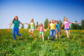 Happy children run and hold hands in green meadow — Stockfoto
