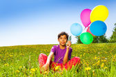 Sitting boy with flying balloons in summer — Stock Photo