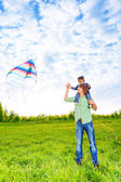 Smiling father holds kid and watches kite in air — Stock Photo