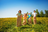 Happy children jump in sacks on green meadow — Stock Photo