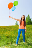 Smiling girl holding three balloons in summer — Stock Photo