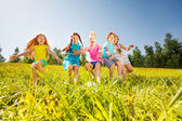 Happy children playing football in yellow meadow — Stock Photo