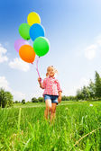 Small blond girl with many balloons in park — Stock fotografie