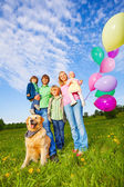 Parents, kids and dog stand with balloons in park — Stock Photo