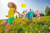 Excited kids with balloons run in field — Stock Photo